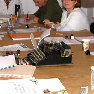 Osoby przy stole z maszyną drukarską