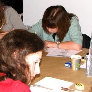 Osoby przy stole piszące na kartkach
