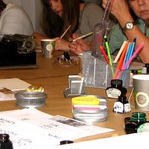 Osoby przy stole na warsztatach z kaligrafii